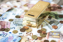 Savings Cash money concept euro banknotes all sizes and cent coins on desk piggy bank gold bar shape save Royalty Free Stock Photography