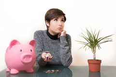 Savings coin in the piggy bank. Young woman thoughtful about savings, coins in the hand and pink piggy bank on desktop Stock Photo