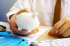 Savings concept. Businessman holding piggy bank. Savings concept. Businessman is holding piggy bank Stock Images