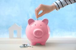 Savings Concept. Female Hand Putting Coin Into Piggy Bank Royalty Free Stock Photo