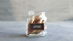 Savings concept, money into a glass. Savings idea. Jar with money and text stock video