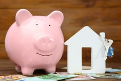 Savings concept. Piggy bank with money and house figure. On wooden table Royalty Free Stock Photo