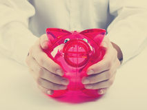 Savings concept. Woman holding piggy coin bank in hands Stock Photography