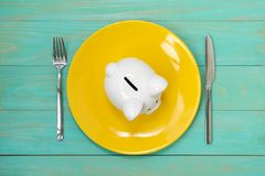 Food expenses,economy and finance,poverty. Savings consumer concept. Piggy bank on the yellow plate with fork and knife stock photos