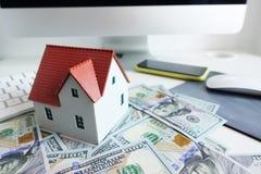 Savings dla nowego i przestronnego domu z miniaturowym klingerytu domem na stosie pieniądze przed komputerem Zdjęcie Stock