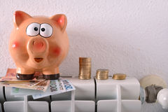 Savings and economy heating with radiator piggy bank and money. Concept savings and economy heating with radiator and piggy bank and stacked coins and bills with Royalty Free Stock Photos