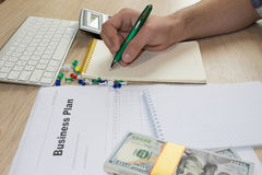 Savings, finances, economy, Business and home concept - man with calculator counting money and making notes at home Stock Image