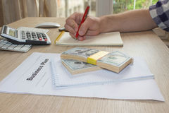 Savings, finances, economy, Business and home concept - man with calculator counting money and making notes at home Royalty Free Stock Photography