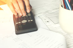 Savings, finances, economy and office concept. Business people counting on calculator Royalty Free Stock Photography