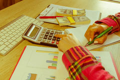 Savings, finances, grant, economy and home concept - Female with calculator, money and making notes at home Stock Photos