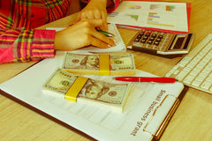 Savings, finances, grant, economy and home concept - Female with calculator, money and making notes at home Stock Images