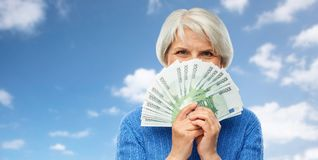 Senior woman with hundreds of euro money banknotes. Savings, finances and people concept - senior woman hiding face behind fan of hundred euro money banknotes stock image