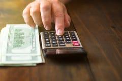 Savings, finanse, gospodarka i domowy pojęcie, - zamyka up mężczyzna z kalkulatora i stosu pieniądze na drewnianym tle obrazy royalty free