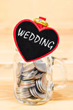 Savings in glass bank and Wedding Ring. Royalty Free Stock Image