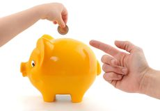 Savings. Hand of a little child and his/her mother in front of a yellow piggy bank Stock Images