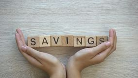 Savings, hands pushing word on wooden cubes, family budget planning, economy. Stock footage stock video