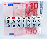 Savings held in Euros. Text  savings  on small white cubes in black uppercase letters with a ten euro note on a reflecting surface Stock Image