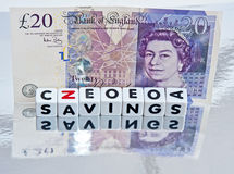 Savings held in pounds Sterling. Text  savings  with black uppercase letters on white cubes and a Bank of England twenty pound note on a reflecting surface Royalty Free Stock Image