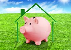 Savings for a house concept, piggy bank on field Stock Photo