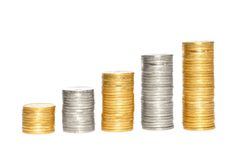 Savings, increasing columns of gold and silvercoins over white Royalty Free Stock Image