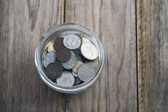 Savings jar. Collection of coins in glass savings jar over wooden table Stock Photos
