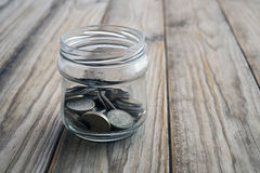 Savings jar. Collection of coins in glass savings jar over wooden table Royalty Free Stock Image