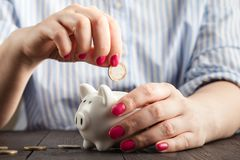 Savings, money, annuity insurance, retirement and people concept - close up of senior woman hand putting coin into piggy bank. Savings, money, annuity insurance stock image