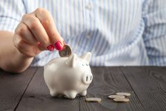 Savings, money, annuity insurance, retirement and people concept - close up of senior woman hand putting coin into piggy bank. Savings, money, annuity insurance stock photo
