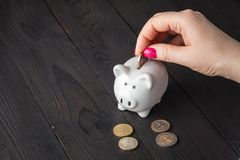 Savings, money, annuity insurance, retirement and people concept - close up of senior woman hand putting coin into piggy bank. Savings, money, annuity insurance stock images