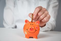 Savings, money, annuity insurance, retirement and people concept. Close up of senior woman hand putting coin into piggy bank royalty free stock image