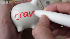 Savings and money for holidays and vacation. Man draws a word travel on a piggy bank stock footage