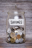 Savings, money jar with coins on wood table Royalty Free Stock Image