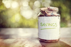 Savings money jar. Full of coins concept for saving or investment for a house, retirement or education Stock Photos