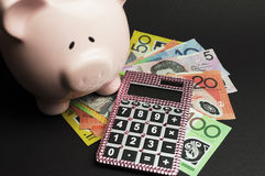 Savings and money management concept with piggy bank. Savings and money management concept with Australian hundred dollar note, pink calculator and piggy bank Stock Images