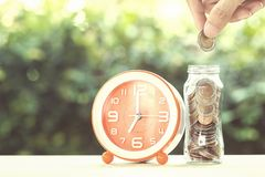 Savings money and time investment concept. Savings money and time investment concept : A man hand putting coin into glass jar with clock time on a table with stock image