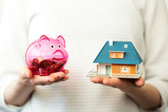 Savings for new family house concept - piggy bank and house scal. Savings for new family house concept - transparent piggy bank and house scale model in hands Stock Photo