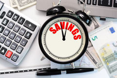 """Savings over time concept suggested by a retro alarm clock with the word """"savings"""" written on its display Stock Photos"""