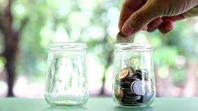 Savings pieniądze w słoju Ręka stawiająca ukuwa nazwę spadać w słój zbiory