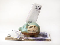 Savings in a Piggy Bank. British twenty pound notes in a Piggy Bank with the words Next Million Stock Images
