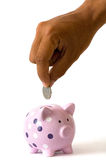 Savings in a piggy bank. A hand placing a coin into a cute piggy bank Royalty Free Stock Images