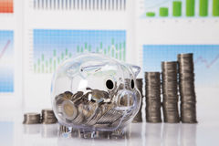 Savings in piggy bank on charts Royalty Free Stock Photography