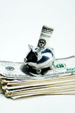 Savings Piggy Bank With Money. A silver piggy bank on top of a pile of money to suggest saving money Royalty Free Stock Photography