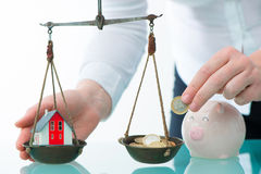 Savings or real estate investment concept. With house and cash money on scale Stock Image
