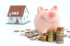Savings for real estate project with small model house  and piggy bank climbing on piles of coins Stock Images