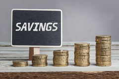 Savings on sign with money stacks. Word Savings in white chalk type on black board, Euro money coin stacks of growth on wood table Stock Images