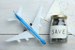 Savings on travel. Toy airplane, savings and map on a wooden background Royalty Free Stock Photography