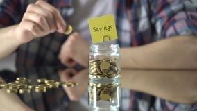 Savings word above glass jar with money, rainy day fund, investment in future