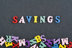 SAVINGS word on black board background composed from colorful abc alphabet block wooden letters, copy space for ad text stock photo