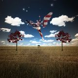 Savior. Surrealism. Naked man with wings in US national colors flies above field of wheat with red trees. Human elements were created with 3D software and are Royalty Free Stock Image