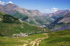 Savoia pastoral summer landscape. Landscape perspective view on mountains, green slops, old village and a road going down the hill Stock Images
